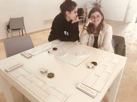 Students sitting next to table with work on as part of the project