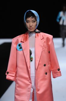 Female model wearing salmon jacket and blue headscarf designed by Hannah Ross