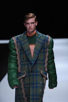 Male model in jacket with tartan body and green puffer sleeves