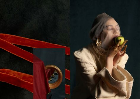 Female model with a veil on eating an apple wearing a white suit and sitting on a red cloth