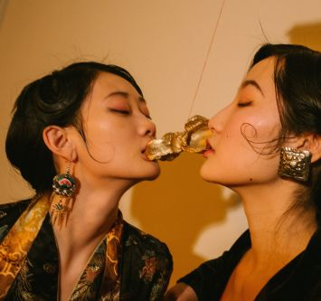 Two female asian models kissing with gold souldered metal between their mouths