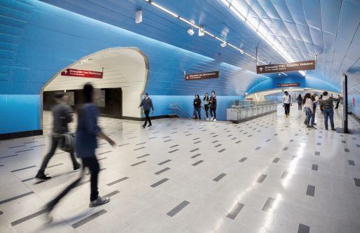 people walking within blue walkway tunnel