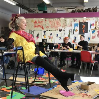 Model in bright yellow, sitting, being drawn in an illustration class