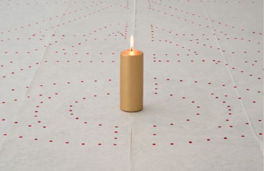 candle on floor with red dot stickers on floor around it