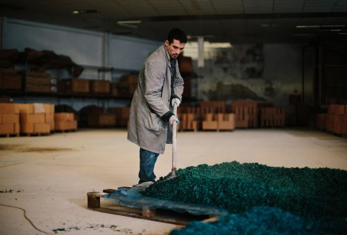 Man sweeping blue material in pile