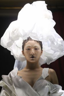 Close up of model wearing white garments and headpiece
