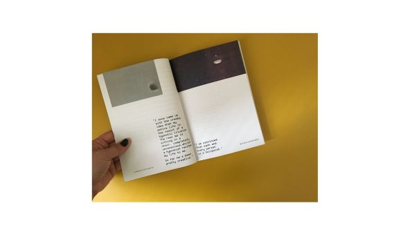 hand holds book on yellow background