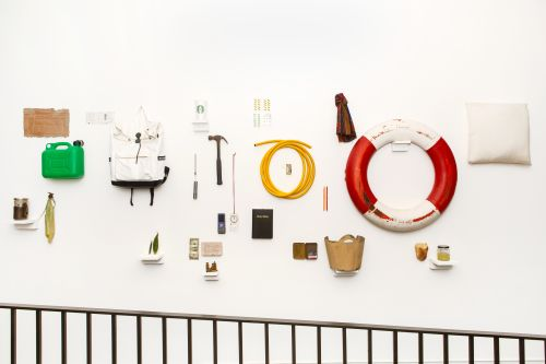 Various objects including a rucksack, a life ring and other tools mounted on the wall as part of Emergence exhibition