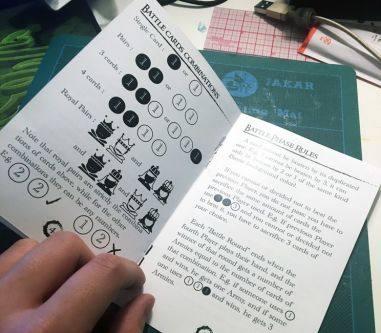 An open rule book for a game designed by student Chris Li. The book shows infographics on Battle Card Combinations.