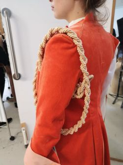Photo of a person wearing a red velvet coat, with gold rope around the arm. Photo taken from the left side