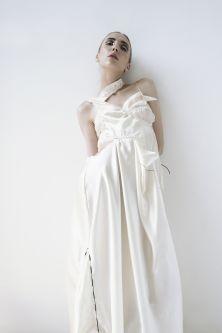 model in slinky patchwork white draped dress