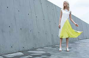 A woman stood on top of a concrete building wearing a white and fluorescent yellow dress