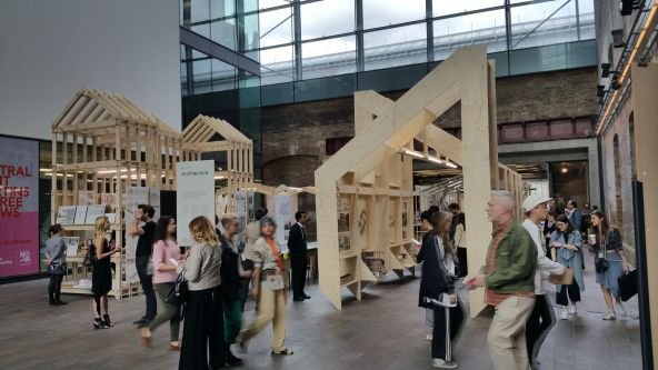 People walking through a series of architectural installations made from a light wood