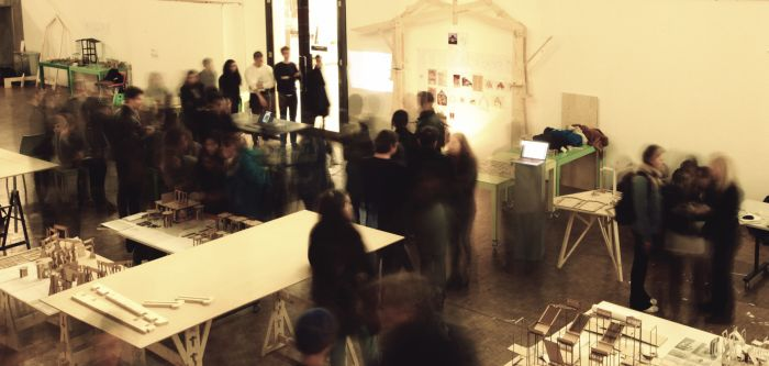 White tables displaying models, model in motion are walking by and observing.