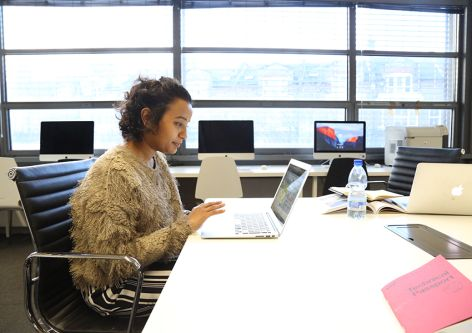 Postgraduate student sitting at a desk on a laptop in the Graduate School space at London College of Communication.
