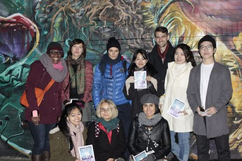 student group photo at night stood up against and east end graffiti wall