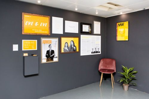 Image of space with two grey walls and one pink chair in the corner. The walls are covered with various posters advertising student work.