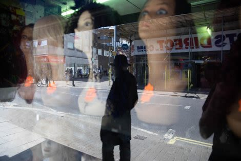 a window of wigs on female manniquins with the street reflection in the window