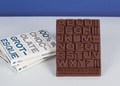 Bar of chocolate made to look like a letter press. Presented next to stacked bars of the chocolate bar in packaging.