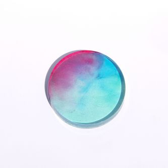 Photo of a petri dish, with the colours baby blue and pink