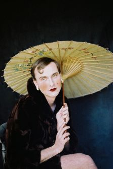 Photograph of male model wearing a fur coat and lipstick holding a parasol