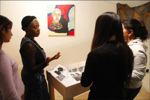 Shannon showing her painting to group of students
