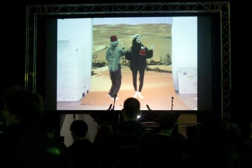 A photograph from behind a crowd watching a large screen showing two women dancing