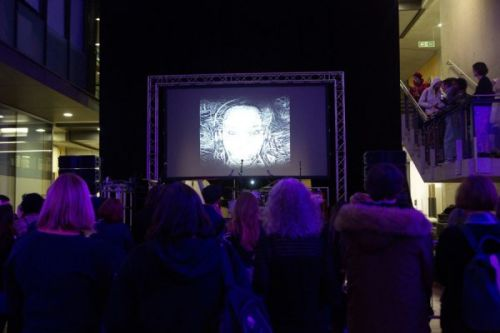 A photograph from behind a crowd watching a large screen above a stage as someone performs