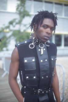 Male model with dreadlocks wearing a black vest with leather panels and silver chain necklace