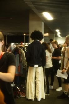 Male model in black and white outfit getting ready backstage