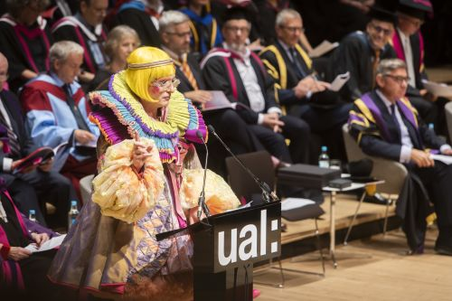 Man wearing brightly colour dress making speech on stage at Graduation