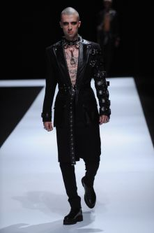 Topless male model with black longline jacket decorated with leather and silver studs