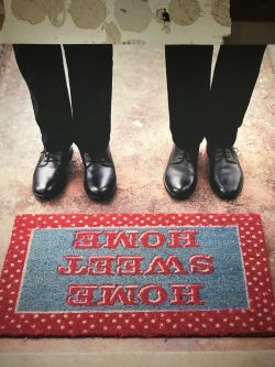 two pairs of polished shoes stepping on rug with the words home sweet home imprinted