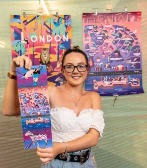 A student prize winner poses with their artwork