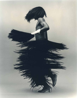 Black and white photograph of model wearing fringed skirt