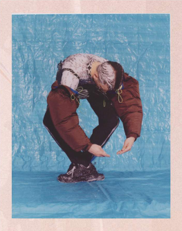 Photograph of man standing on tarpaulin in a puffer jacket