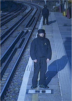 Photograph of a train platform with men standing on it in a CCTV style