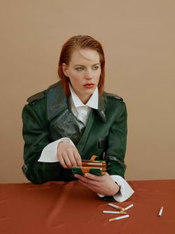 Ginger lady in green trench coat sitting at a table with a box of cigarettes