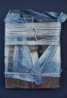 Folded denim bound by wool yarn by Emma McGinn.