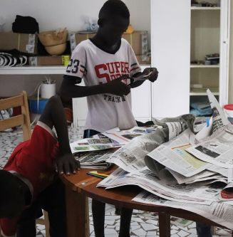 2 young boys cutting up newspapers