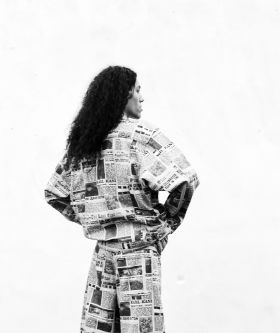 Photograph of a man wearing a newspaper print denim jacket, shot from the back