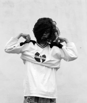 Photograph of a person putting on a sweat shirt with a Wu-Tang logo