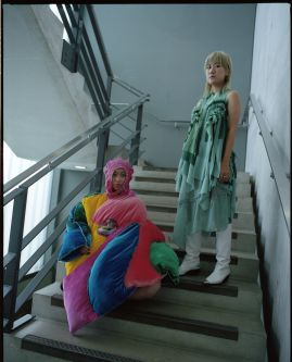 Two models in Emily's fashion designs. They are colourful, long dresses.