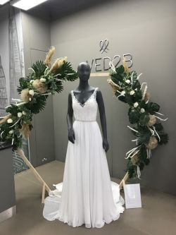 A photo of a mannequin wearing a long white dress with the logo WED2B on the wall behind.