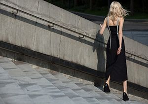 A woman walking down some concrete steps wearing a black dress