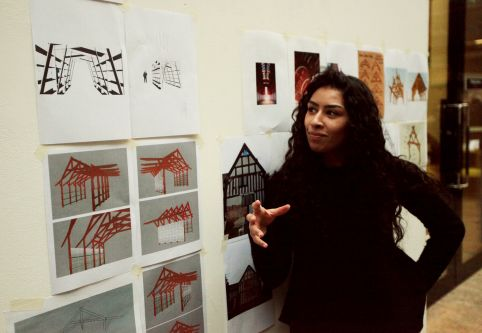 A person mid discussion next to a pages of architectural drawings