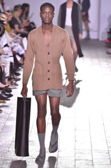 A model walking down a catwalk holding a black bag and wearing a camel coloured jacket and grey shorts