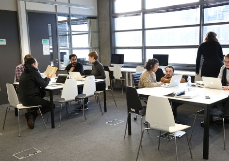 Postgraduate students sitting at tables, with laptops within the Graduate School Space in London College of Communication.