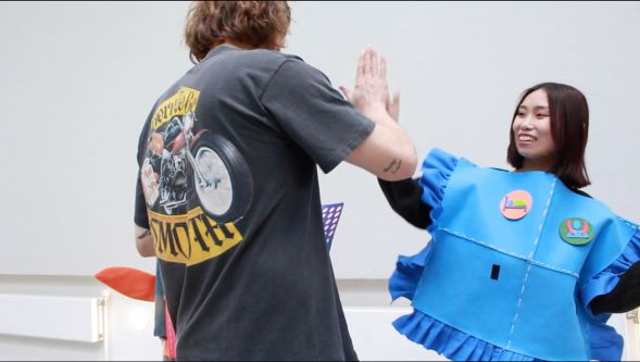 Student dressed in blue outfit high-fiving
