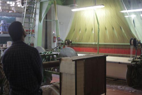 Ranura looking up at a large knitting machine